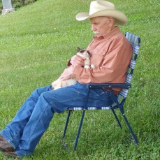 Gene gets in an afternoon 'catnap' with one of the many cats on the farm. - Darrel Nelson
